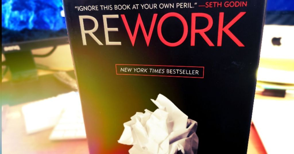 Cover of Rework on a busy desk.
