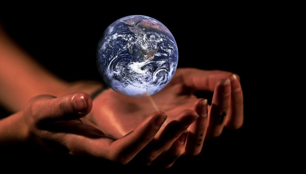 Cupped hands, palms up, hold a luminous earth against a black background.