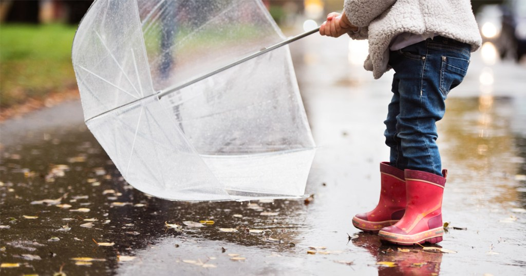 A child holds an umbrella, and has red boots.