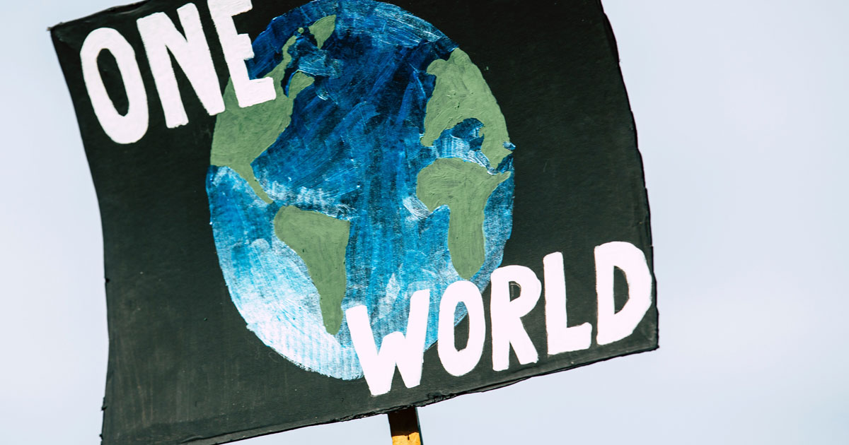 """A sign is held up that is a painting of the earth with """"one world"""" written over top."""