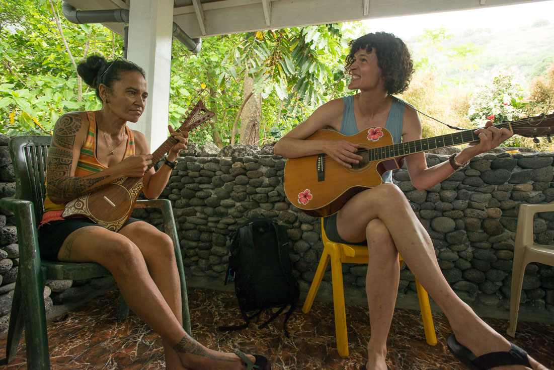 Two women sit in chairs and one plays guitar, the other the ukulele.