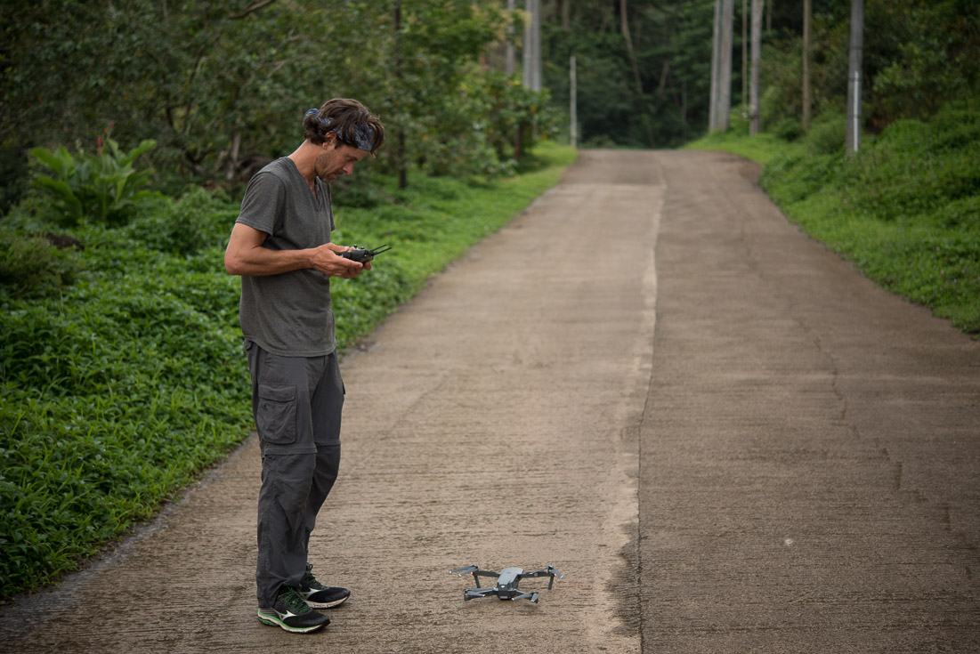 A man stands above his drone on a dirt road, preparing to use the console to make it fly.