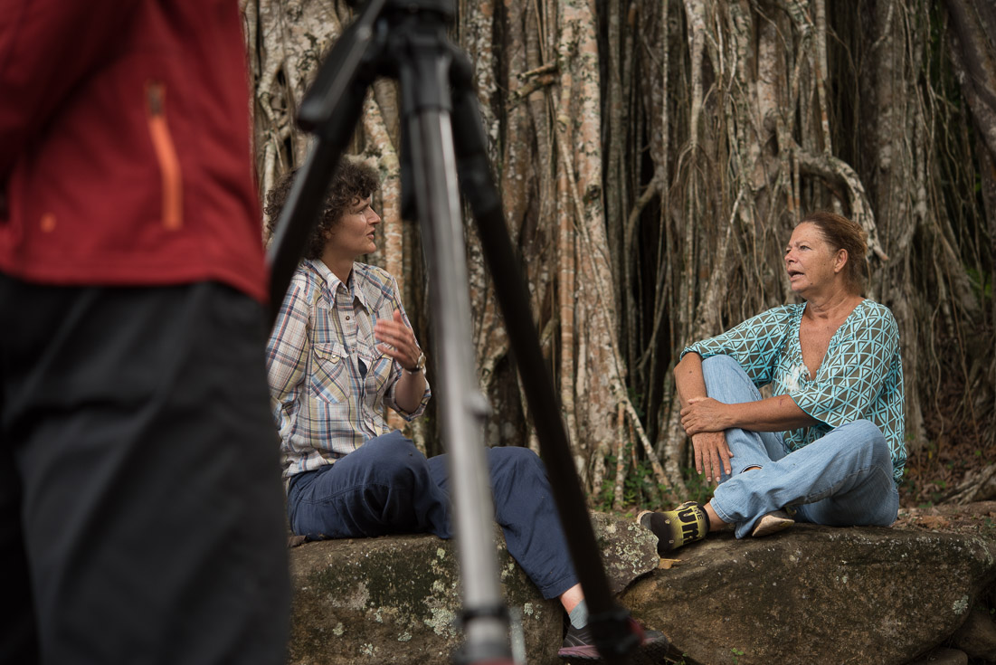 Two women sit on a rock having a discussion while a camera on a tripod films them.