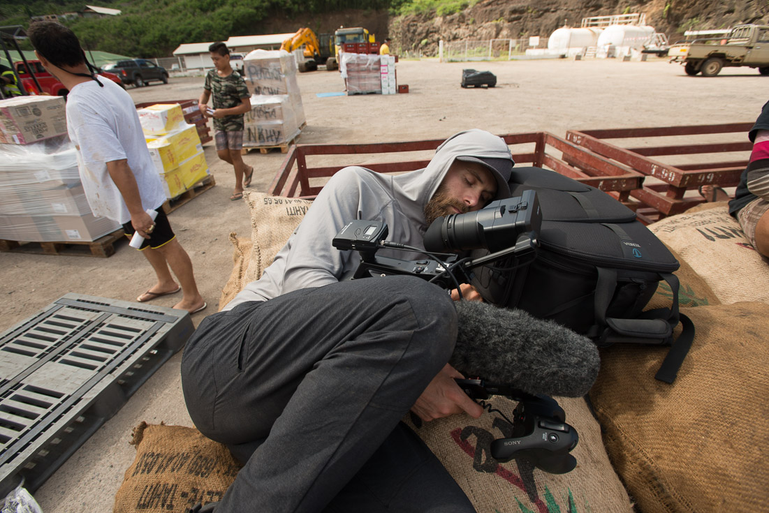 A cameraman lies on the ground in a construction site to get his shot while two people stand a few feet away in the background.