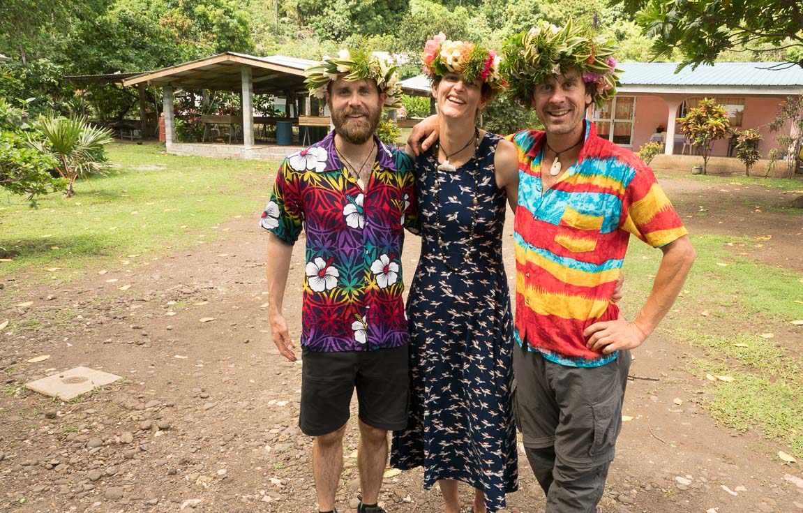 A woman in a dress poses with one man on either side of her while they all wear flower crowns.