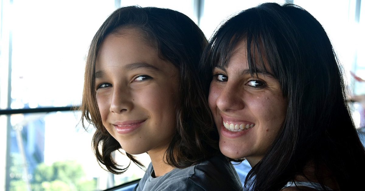 A woman and a child facing left turn to look at the camera smiling with their heads leaning together.